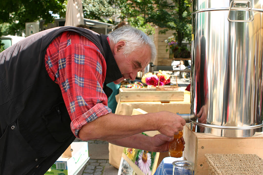 Jørgen tapper honning på fødevaremarked. Foto: © Maria Gram